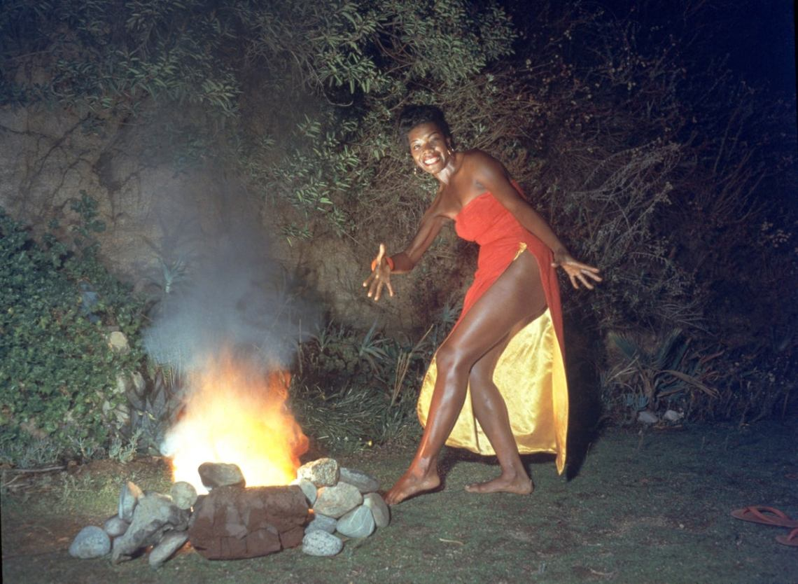 maya-angelou-wears-a-red-dress-while-dancing-next-to-a-fire-in-a-promotional-portrait-taken-for-the-cover-of-her-album-miss-calypso-1957 - essence